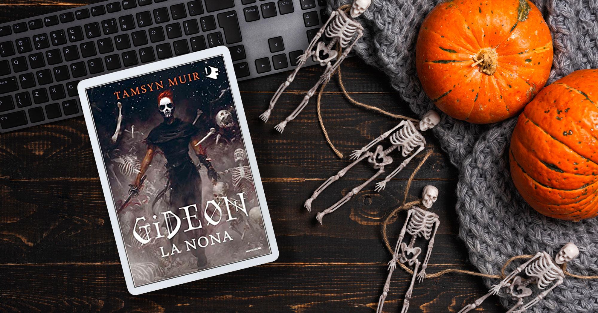 """iPad con la copertina di """"Gideon. La nona"""" su un tavolo con scheletri e zucche"""