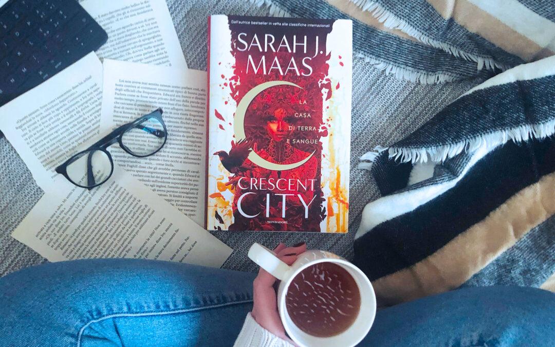"""Ragazza con le gambe incrociate e con in mano una tazza di te con di fronte il libro """"Crescent city"""" di Sarah J. Maas"""