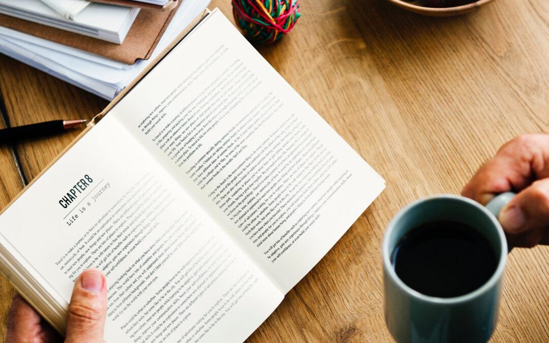 Mani che reggono un libro aperto e una tazza di caffè sopra un tavolo in legno
