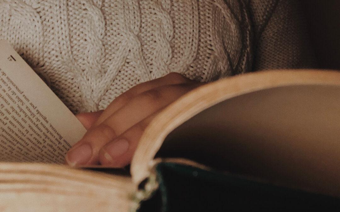 Primo piano di un libro tenuto aperto con una mano che tiene un segnalibro