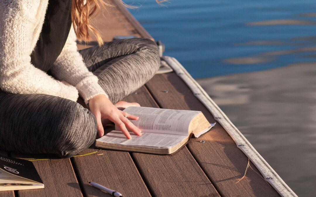 Ragazza che legge a gambe incrociate su una banchina al lago