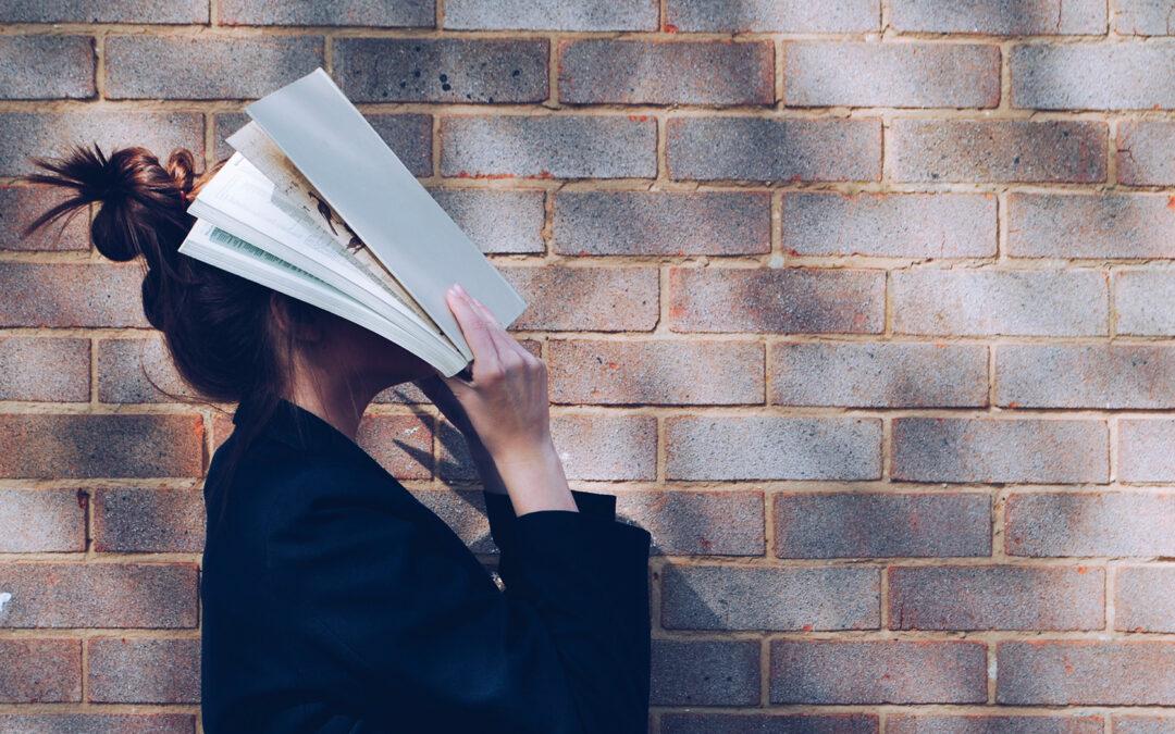 Ragazza di profilo con la faccia in un libro