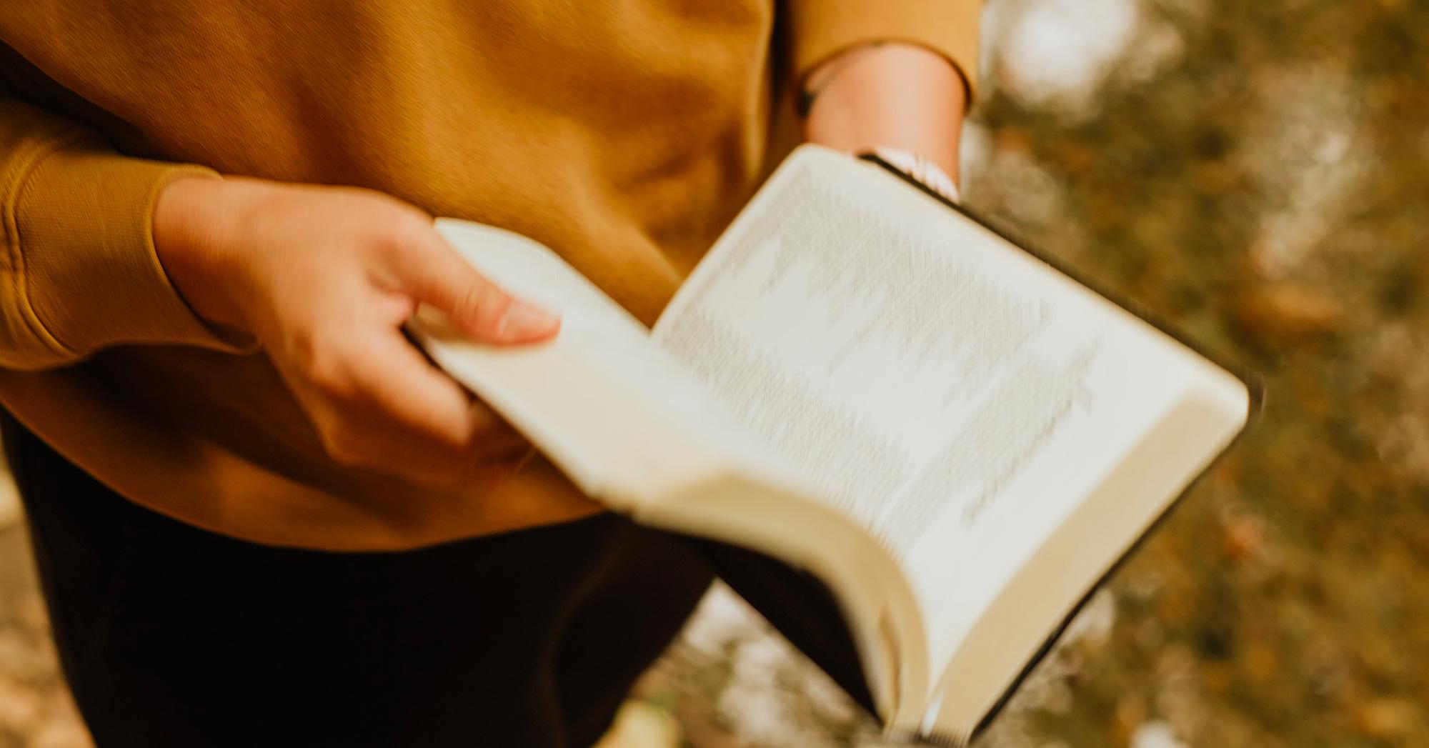 Libro aperto tra le mani di una ragazza