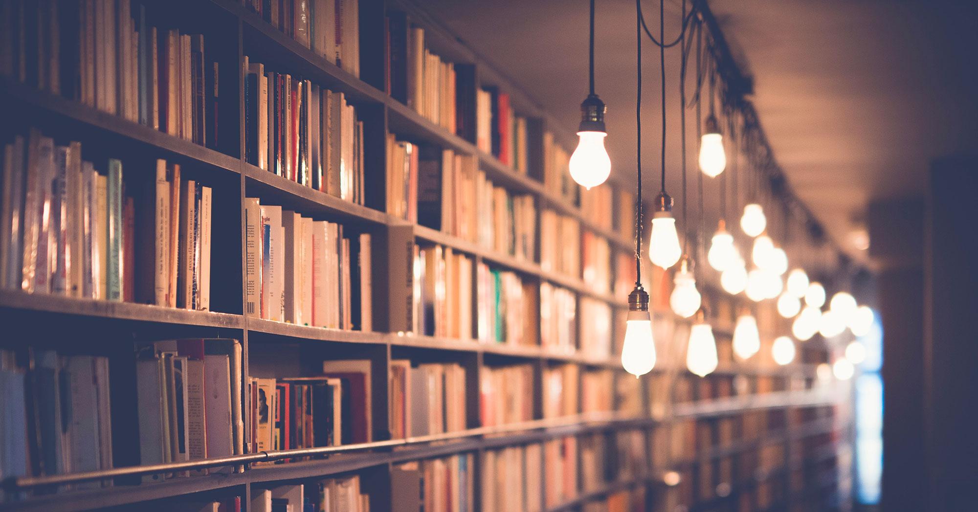 Libreria illuminata da lampadine che scendono dal soffitto