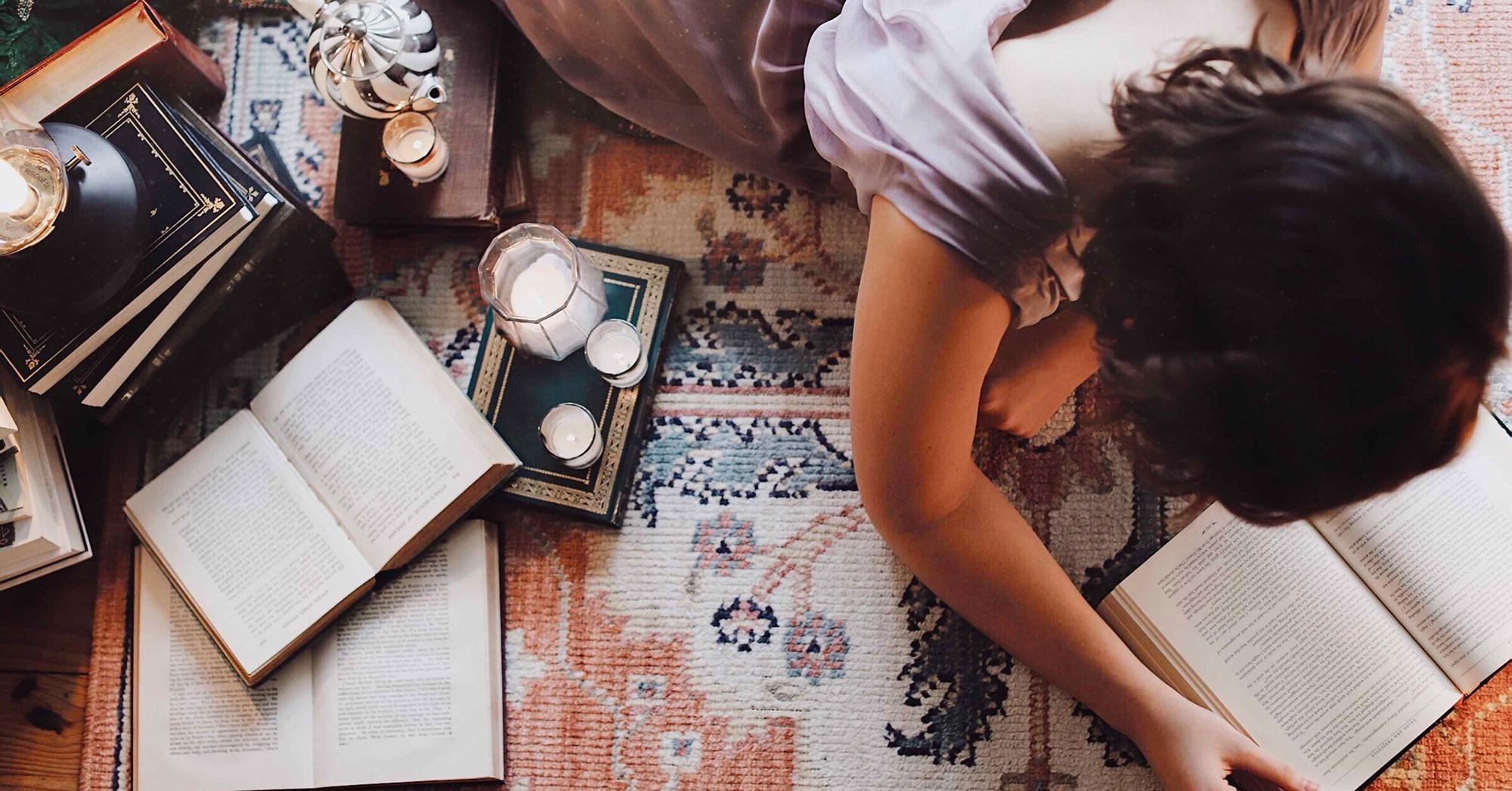 Foto dall'alto di ragazza sdraiata che legge